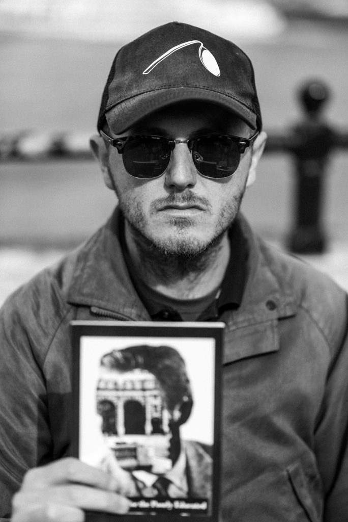 Black and white street portrait of man in baseball cap holding a book