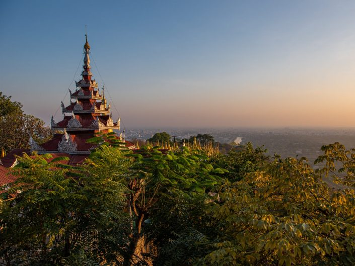 Landscape at sunset from the top of a hill with a temple roof visible