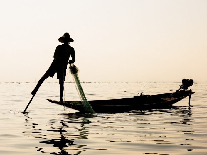 Silhouette of Myanmar fisherman on a boat at sunset