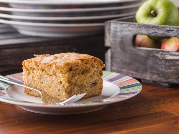 Piece of cake on a plate with apples in the background