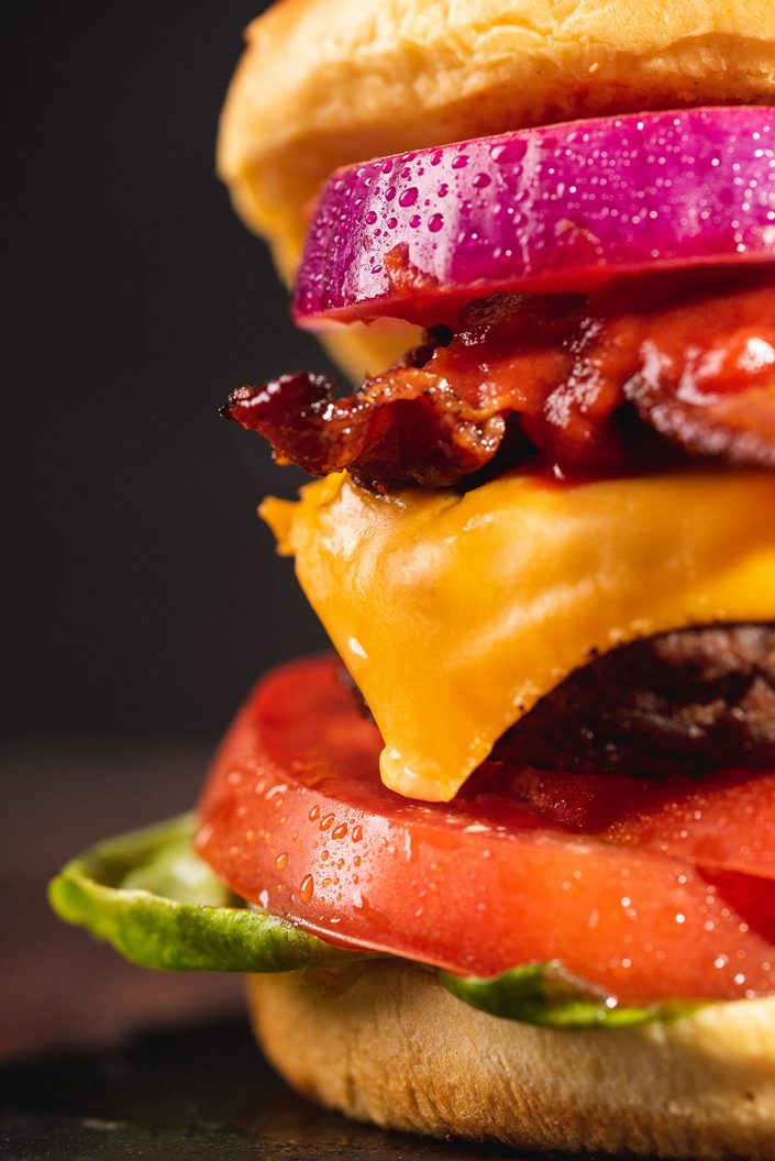 Close up of a bacon cheeseburger with onions, tomato and lettuce