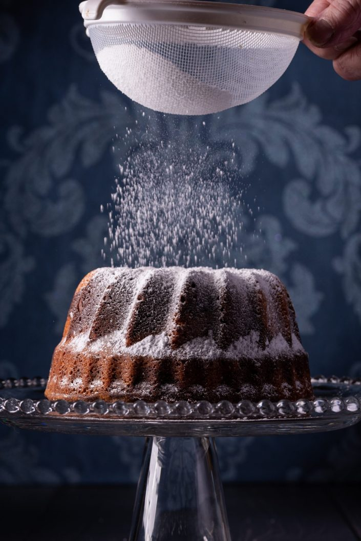 icing sugar being sprinkled onto a chocolate bunt cake