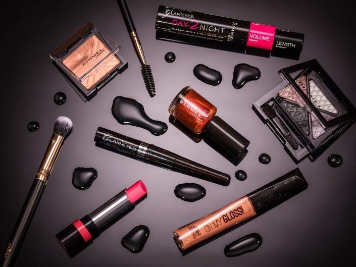 Flat lay of Rimmel Product on Black background with water droplets
