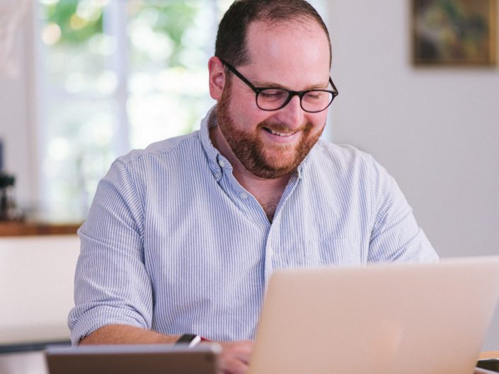 Man laughs as he is working on a laptop