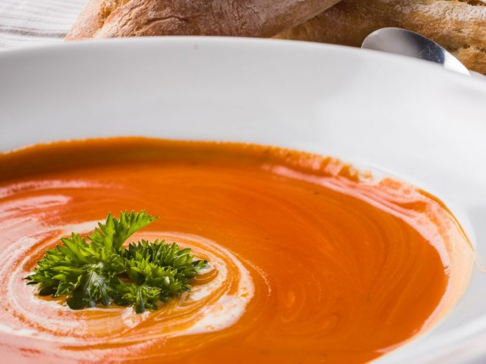 Tomato soup in a white bowl with bread