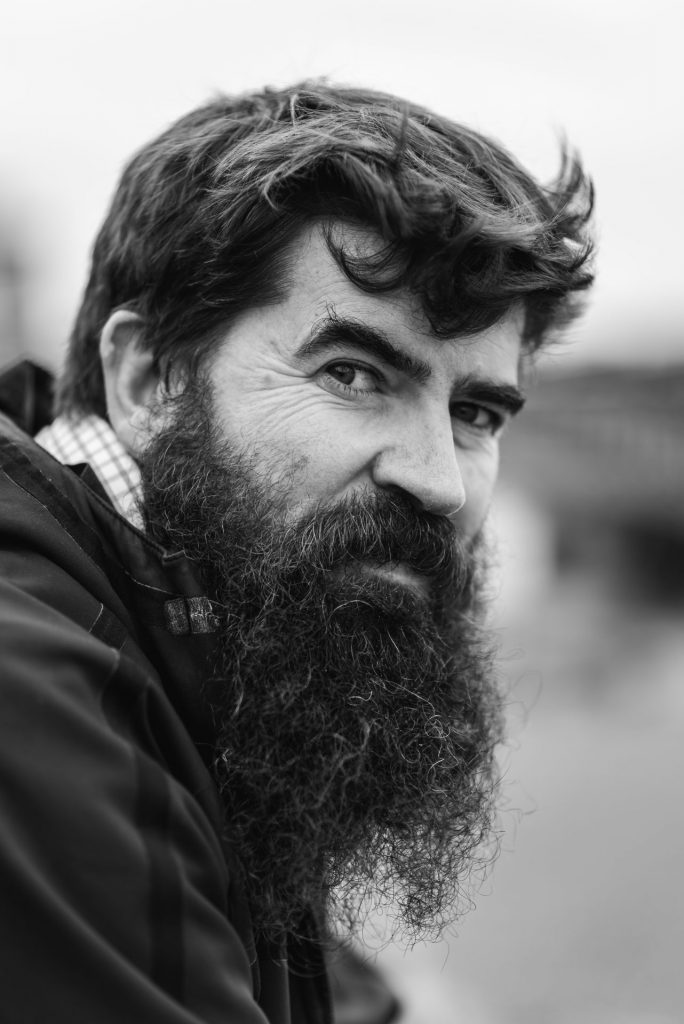 Black and white street portrait of man with long black beard