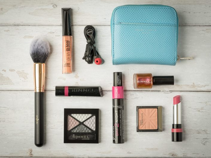 flat lay of rimmel london products on white woodboard