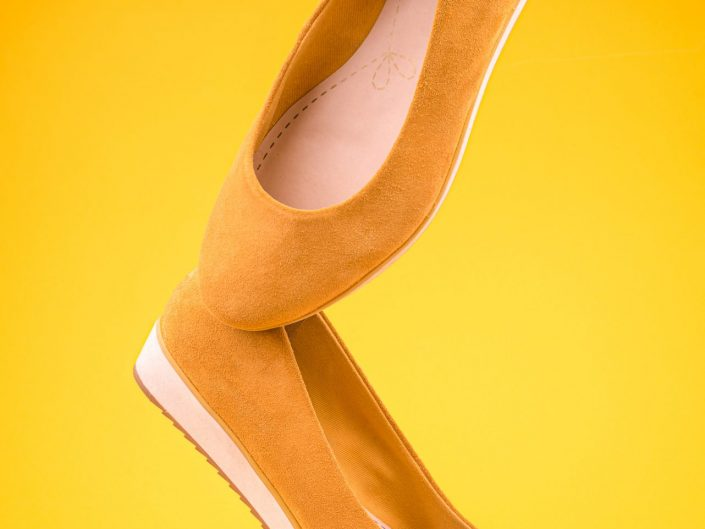 Yellow womens sued shoes floating on a yellow background