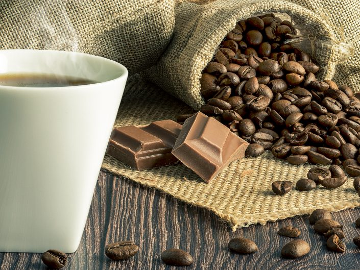 A steaming cup of coffee with coffee beans and chocolate on hessian sacks