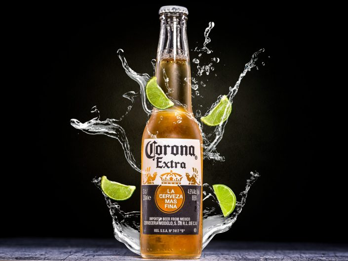 A bottle of Corona with water splashes and lime wedges